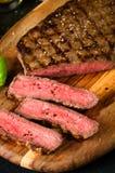 切好的罕见的牛排胡椒盐大蒜刀子 免版税库存图片