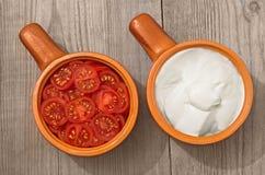 切好的蕃茄和酸性稀奶油在盘在桌上 免版税库存图片