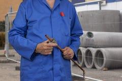 切开一个铜管子的建筑工地的水管工 免版税库存图片