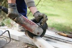 切开一根钢筋混凝土柱子的建筑工人 库存图片