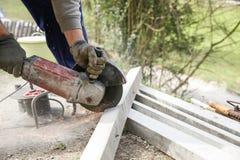 切开一根钢筋混凝土柱子的建筑工人 免版税库存照片