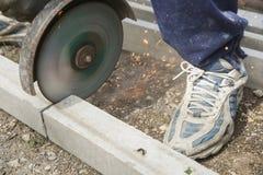 切开一根钢筋混凝土柱子的建筑工人 免版税库存图片