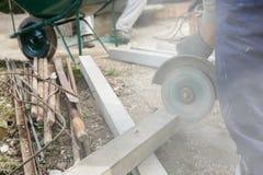 切开一根钢筋混凝土柱子的建筑工人 库存照片