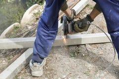 切开一根钢筋混凝土柱子的建筑工人 免版税图库摄影