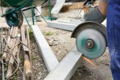 切开一根钢筋混凝土柱子的建筑工人 图库摄影