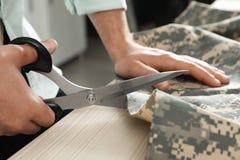 切开与剪刀的专业裁缝伪装织品在车间 免版税图库摄影