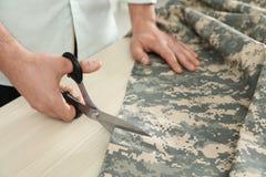 切开与剪刀的专业裁缝伪装织品在车间 免版税库存图片