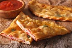 切开与火腿和乳酪特写镜头的意大利薄饼calzone horizont 库存图片