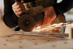 切开与许多锋利的火花的产业工人金属 对切割机的选择焦点 Copyspace 图库摄影