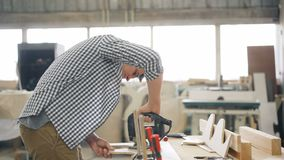 切开与fretsaw的杂物工木头使用电仪器在车间 股票录像