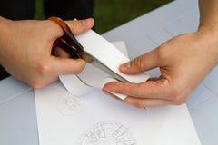 切开使用剪刀的板料纸 库存照片