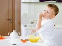 切开品尝他的面团混合物的小厨师 免版税库存图片