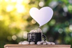 切开在一个咖啡杯的心脏纸在一个木板和Bokeh树背景 库存图片