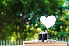 切开在一个咖啡杯的心脏纸在一个木板和Bokeh树背景 免版税库存图片