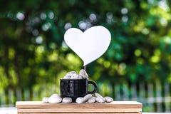 切开在一个咖啡杯的心脏纸在一个木板和Bokeh树背景 免版税库存照片