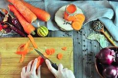 切开在厨房板的两只女性手一棵菜 免版税库存照片