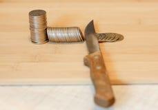 切开堆硬币的刀子 削减预算,储款, r的概念 免版税图库摄影