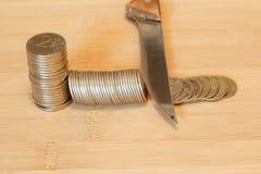 切开堆硬币的刀子 削减预算,储款, r的概念 免版税库存照片