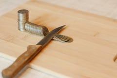 切开堆硬币的刀子 削减预算,储款, r的概念 库存照片