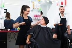 切开女性客户的愉快的妇女美发师 免版税库存图片