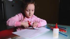 切开她的图画的桃红色毛线衣的逗人喜爱的矮小的学龄前欧洲女孩孩子在纸板料外面,谈话与某人 股票视频
