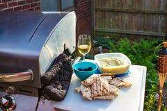 切开平的面包并且浸洗和橄榄和一杯白葡萄酒坐在外部气体格栅旁边的一个切板与烤箱mi 库存图片