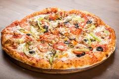 切开成比萨饼用蕃茄、橄榄、香肠和乳酪在一个木盛肉盘 库存图片