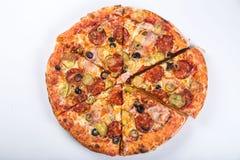 切开成比萨饼用蕃茄、橄榄、香肠和乳酪在一个木盛肉盘 免版税库存照片