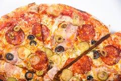 切开成比萨饼用蕃茄、橄榄、香肠和乳酪在一个木盛肉盘 库存照片