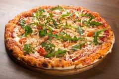 切开成比萨饼用蕃茄、橄榄、香肠和乳酪在一个木盛肉盘 免版税图库摄影