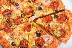 切开成比萨饼用蕃茄、橄榄、香肠和乳酪在一个木盛肉盘 免版税库存图片