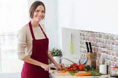 切开新鲜蔬菜的美丽的少妇在厨房里 库存图片