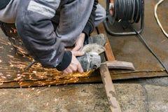 切开有一台手工电研磨机的产业工人一支金属正方形管 库存照片