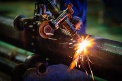 切开有乙炔焊切割吹管的a的工作者钢管 库存照片