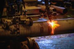 切开有乙炔焊切割吹管的a的工作者钢管 库存图片