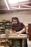 切开木板条的工匠在他的有安全齿轮的车间 库存照片