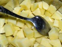 切开未加工的土豆和匙子在平底深锅 图库摄影