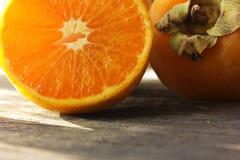 切开桔子和柿子 库存图片