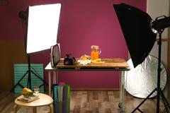 切开桔子和水罐用汁液在桌上 免版税库存照片