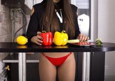 切开沙拉的内衣的美女菜,当烹调在厨房里时 图库摄影