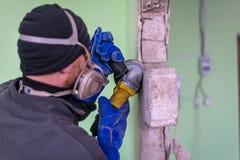 切开混凝土墙的建筑工人通过使用电切削刀 库存照片