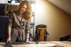 切开灰色织品的相当被聚焦的年轻女人时尚编辑在演播室 库存照片