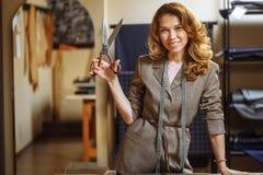 切开灰色织品的相当被聚焦的年轻女人时尚编辑在演播室 图库摄影
