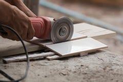 切开瓦片的建筑工人使用角度研磨机 免版税库存照片