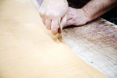 切开皮革的皮革工作者 库存照片