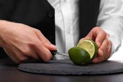 切开石灰的侍酒者的特写镜头,隔绝在白色背景 做概念的一名甜,酸果子圆滑的人 库存图片