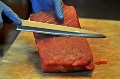 切开红色金枪鱼的Cheff在餐馆 免版税库存照片