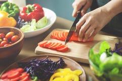 切开红萝卜或菜的女性手 免版税库存图片