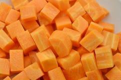 切开红萝卜立方体在木土气,顶视图的 免版税库存照片
