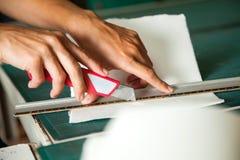 切开纸的手使用在表上的刀片 免版税库存图片